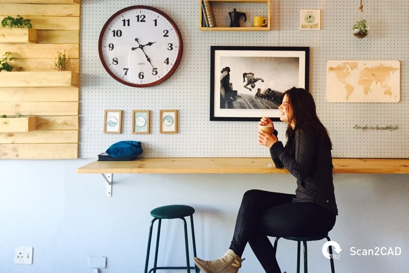 Woman seated at bench drinking coffee