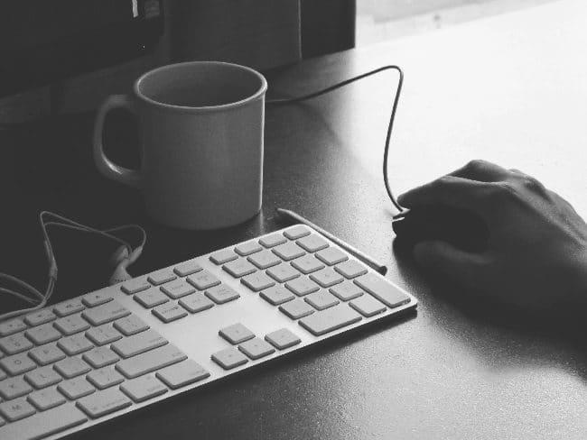 Hand using mouse next to computer and mug