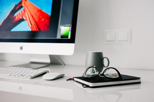 Desk with Mac. glasses and book.