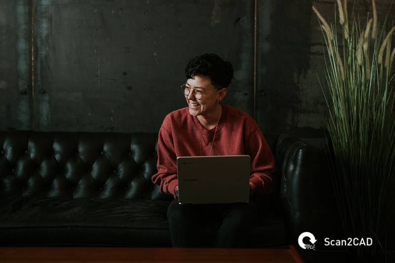 person with a laptop, smiling on a sofa